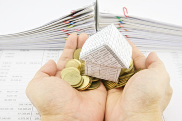 Man holding paper house on pile gold coins