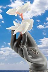 main de bronze offrant des fleurs de frangipanier