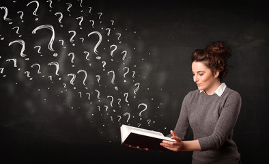 Pretty woman reading a book with question marks coming out from