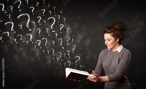 Pretty woman reading a book with question marks coming out from - 70471927