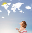 canvas print picture - Young girl looking at world clouds and sun on blue sky