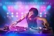 Obrazy na płótnie, fototapety, zdjęcia, fotoobrazy drukowane : Disc jockey mixing music on turntables on stage with lights and