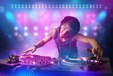 Fototapety Disc jockey mixing music on turntables on stage with lights and