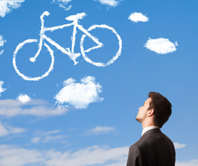 Young man looking at bicycle clouds on blue sky