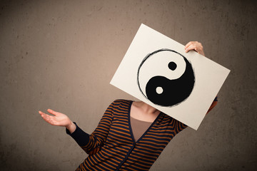 Woman holding a paper with a yin-yang on it in front of her head