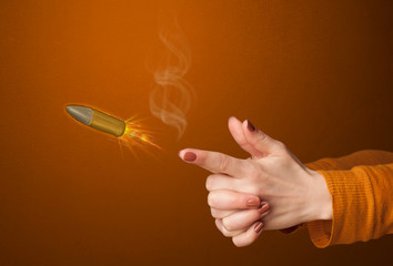 Gun shaped woman hand with bullet