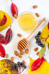 Honey with nuts in autumn leaves