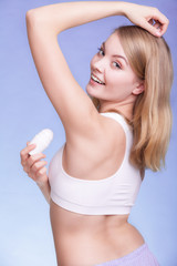 Girl applying stick deodorant in armpit. Skin care