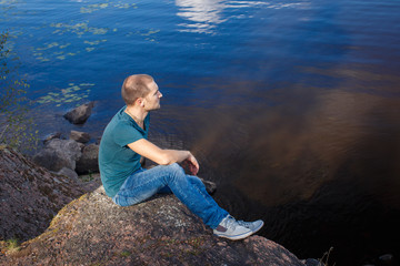 Sad man sitting on a rock by the lake