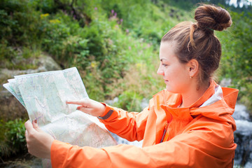 Attractive young female tourist looking into map (shallow DOF)