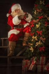 Santa Claus decorating Christmas tree in dark room