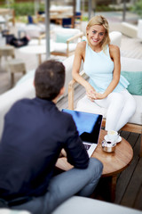 Young businesswoman discussing plan with male colleague at meet