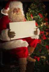Santa Claus holding sign near Christmas tree