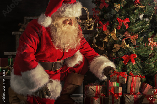 Santa is placing gift boxes under Christmas tree - 70478393