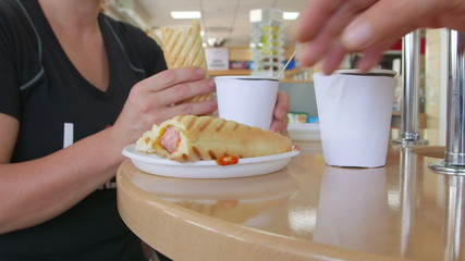 Couple eating hot dogs with coffee at table in grocery store