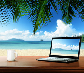 notebook on table and tropical beach