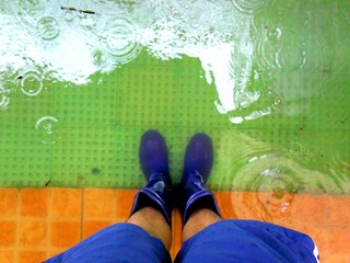Feet wearing rubber boots standing on flood water