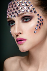 Luxury woman with rhinestones on her face