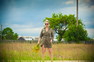 Beautiful girl with a yellow bouquet in hand. Countryside