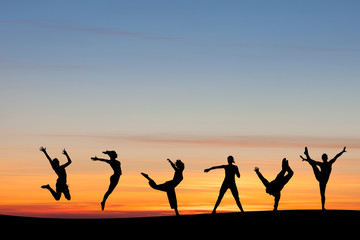 silhouetted group tumbling and dancing in sunset