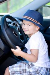 Cute driver in blue hat sits in car