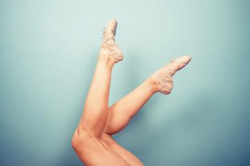 Slender female legs in ballet slippers