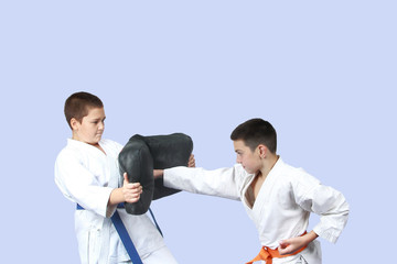 Athlete with an orange belt strikes a blow to simulator