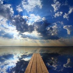 wooden pier on big lake and sky reflection