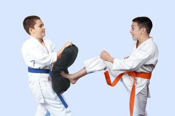 With orange belt an athlete beats a karate kick on the simulator