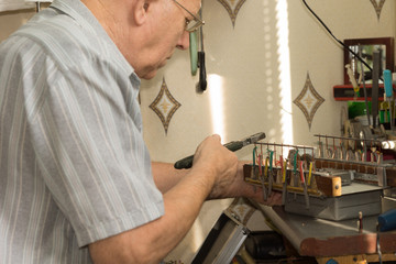 Old Man Working Electronic Device Using Pliers