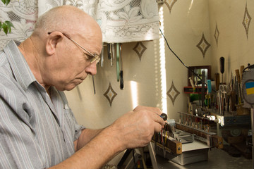 Serious Old Man Working For Electronic Device