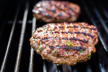 Hamburgers on the grill with stripes outdoors