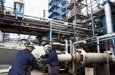 oil workers with main fuel-pumps inside refinery industry