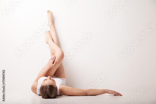 Leinwanddruck Bild Beautiful woman legs raised up high lying
