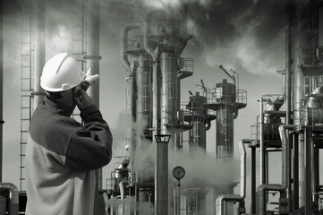 oil worker pointing at refinery, smoke and smog
