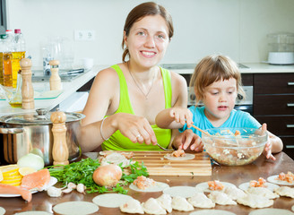mother with daughter making fish dumplings at home kitchen