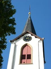 Kirchturmspitze mit Turmuhr vor blauem Himmel in Leopoldshöhe