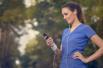 Lächelnde attraktive Frau hört Musik zum Jogging