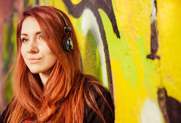 young woman listening music at colorful wall