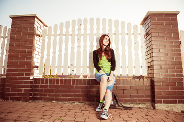 young redhead woman at street fence