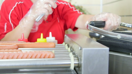 Sausages for hot dogs on rotating grills in fast food