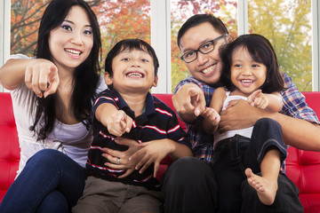 Cheerful asian family pointing at camera