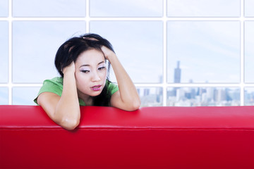 Close-up depressed female on red sofa indoor