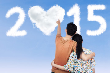 Couple pointing at heart shaped cloud