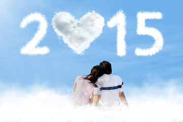 Couple sitting on cloud with number 2015