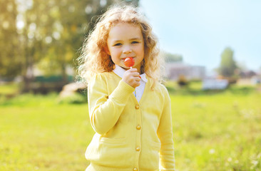 Little child with sweets outdoors