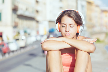 Beautiful Girl with Headphones Listening Music in the City