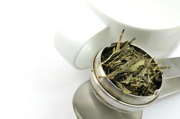 Teesieb mit grünem Tee und Tasse