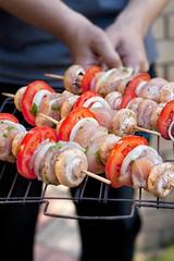 Raw chicken kebabs in male hands