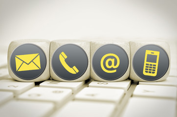 Website and Internet contact us icons on cubes on a keyboard